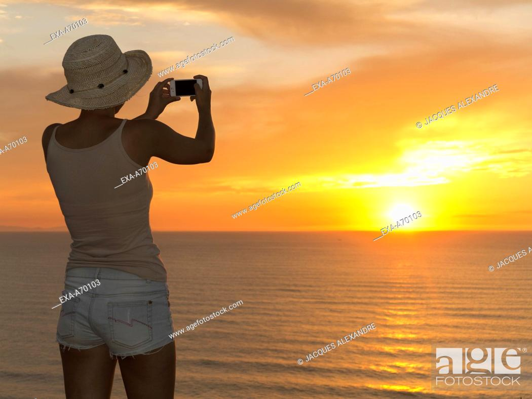 Imagen: Woman with sun hat, back view, photographing sunset at sea.