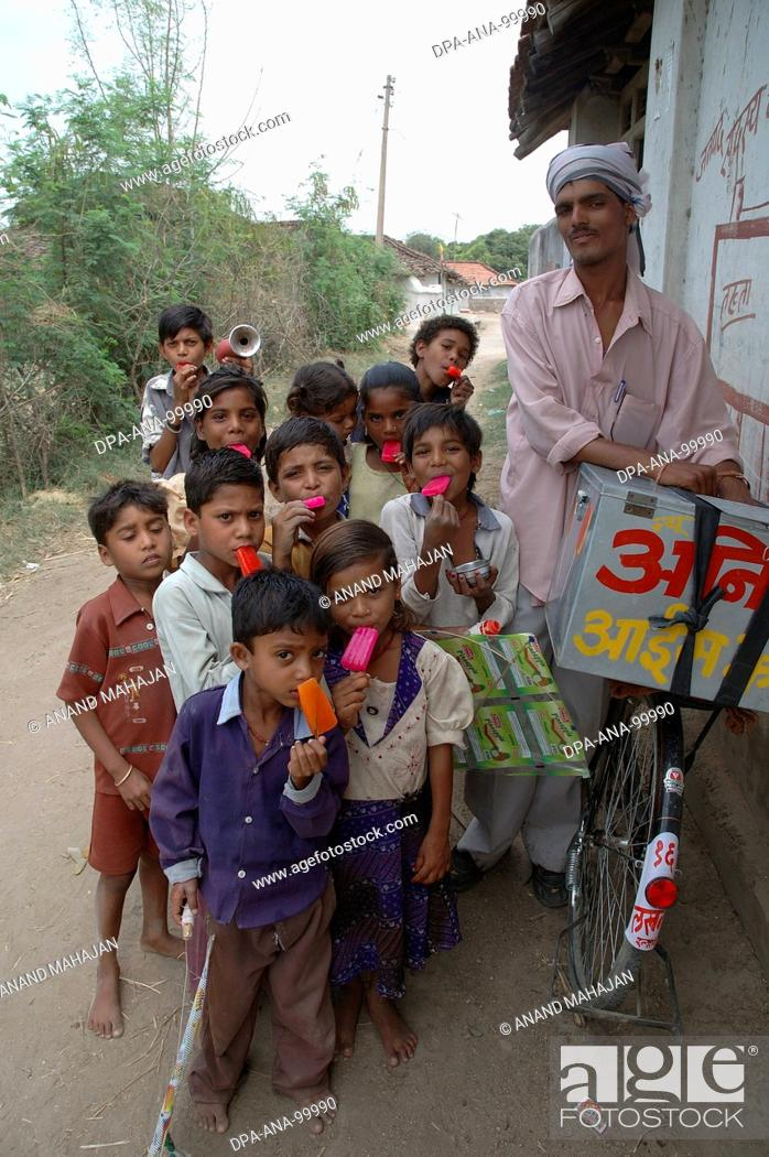 Stock Photo: School going children eating red color ice cream , Village Manghawa , District Narsinghpur , Madhya Pradesh , India.