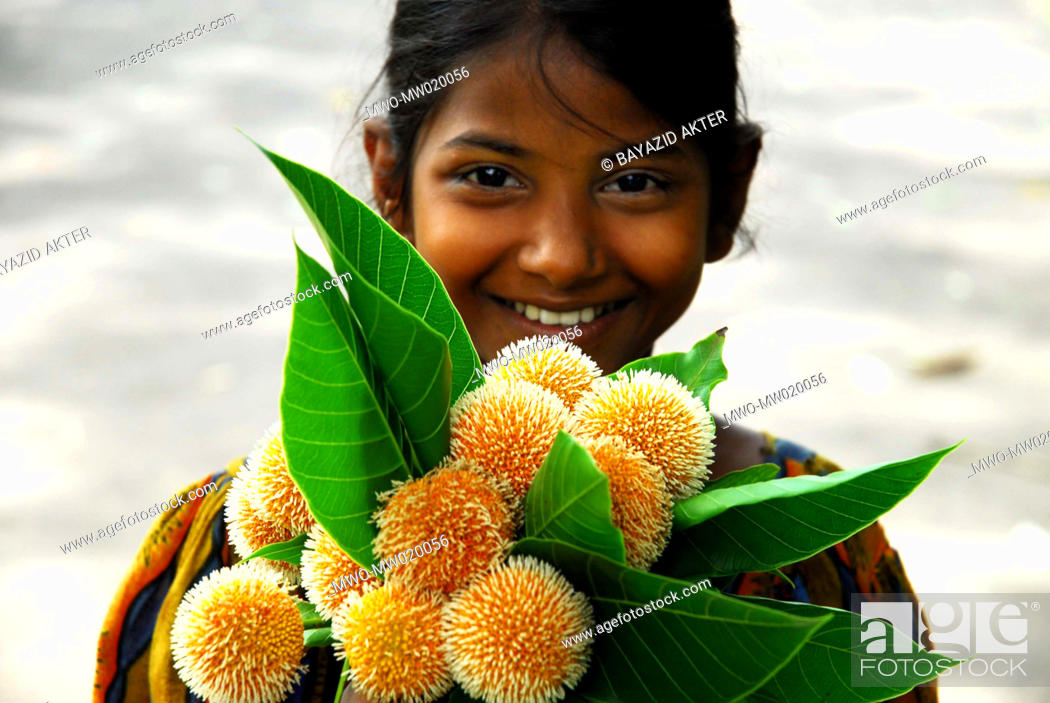 Stock Photo: Portrait of a smiling girl who came to the Dhaka University Campus, to sell Kadam flowers, on the first day of the Bangla month Ashar rainy season Kadam flower.