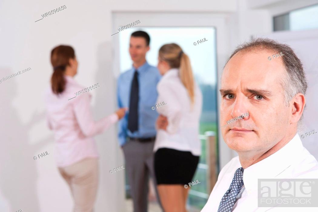 Stock Photo: Seious businessman with businesspeople in the background, portrait.