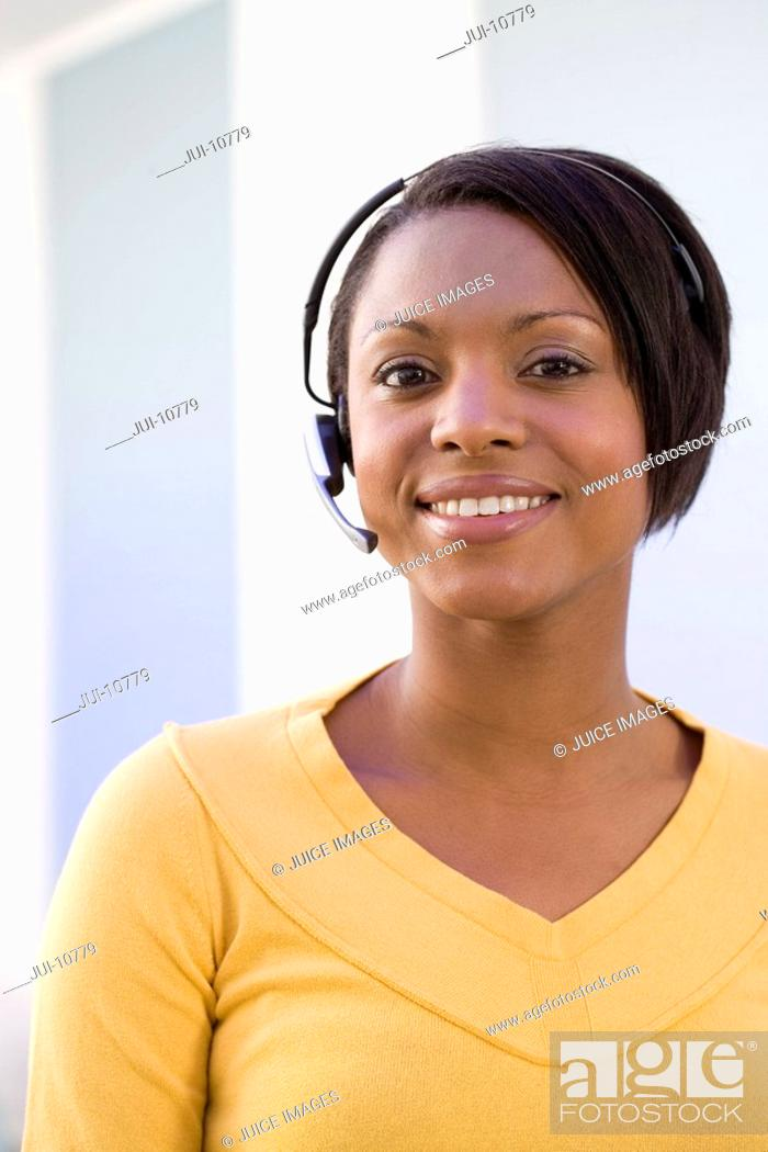 Stock Photo: Young businesswoman in headset, smiling, portrait, close-up.