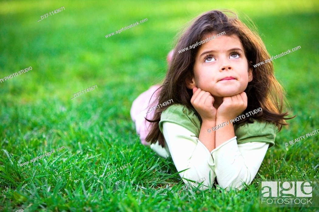 Stock Photo: Pretty girl laying on the grass thinking.
