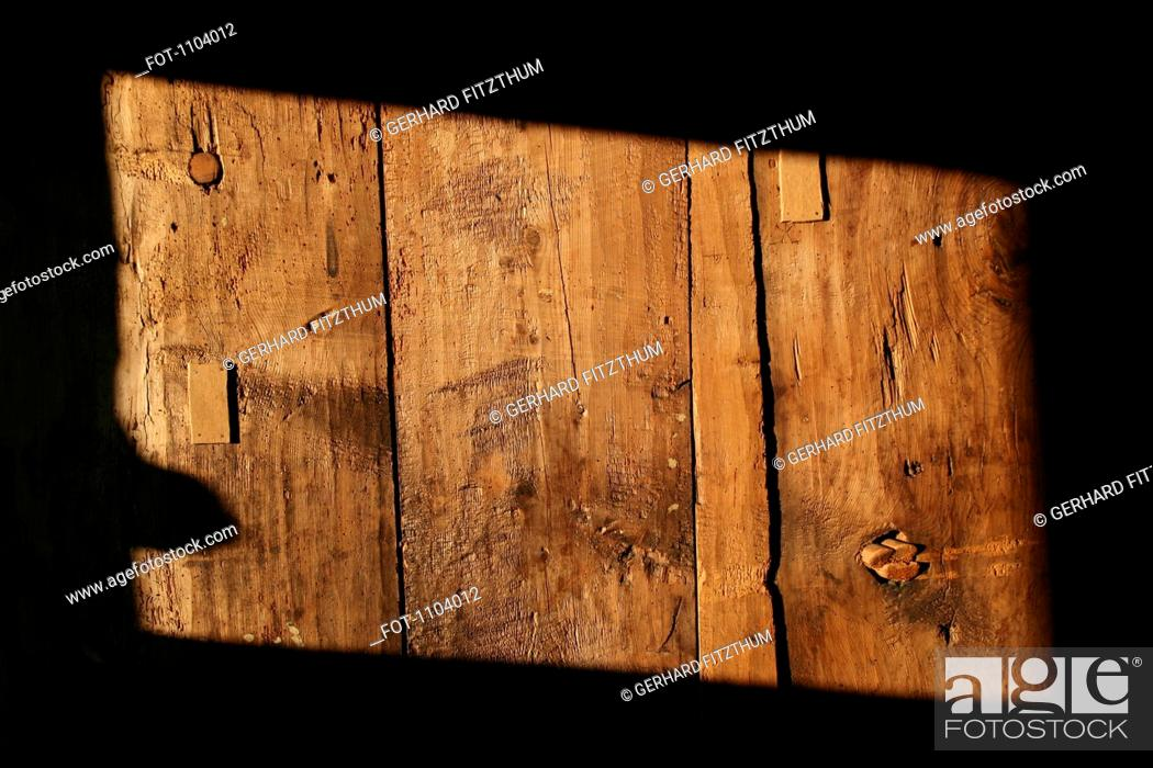 Stock Photo: A rectangle shape of sunlight on a wooden structure, close-up.