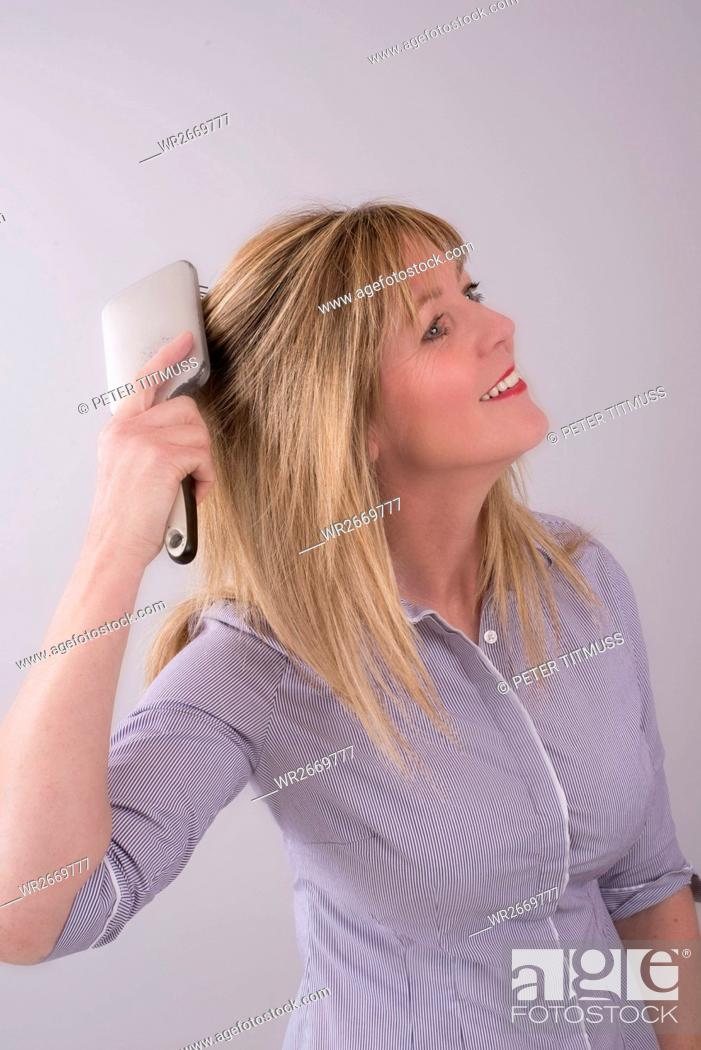 Stock Photo: Portrait of a woman brushing her hair.