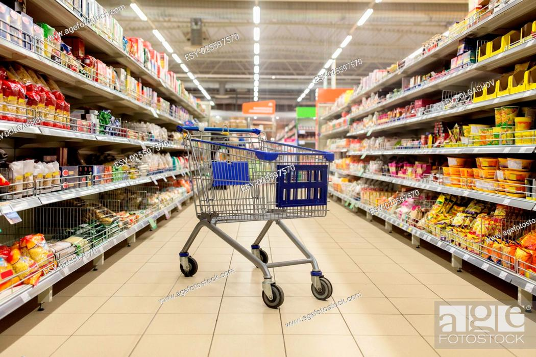 Stock Photo: consumerism concept - empty shopping cart or trolley at supermarket.