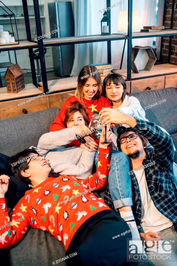 Photo de stock: Group friends talking sitting in a couch in the living room. Everyone holds glasses in their hands.