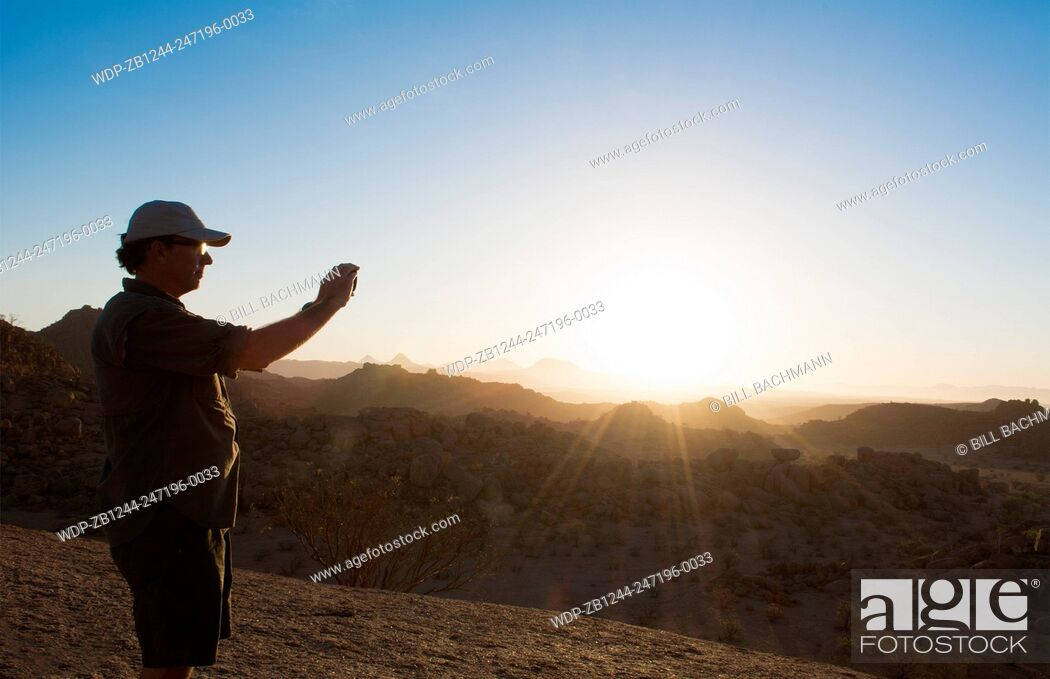 Imagen: Namibia Africa sunset tourists taking photos at Damaraland at resort called Mowani Mountain Camp with beautiful rock formations.