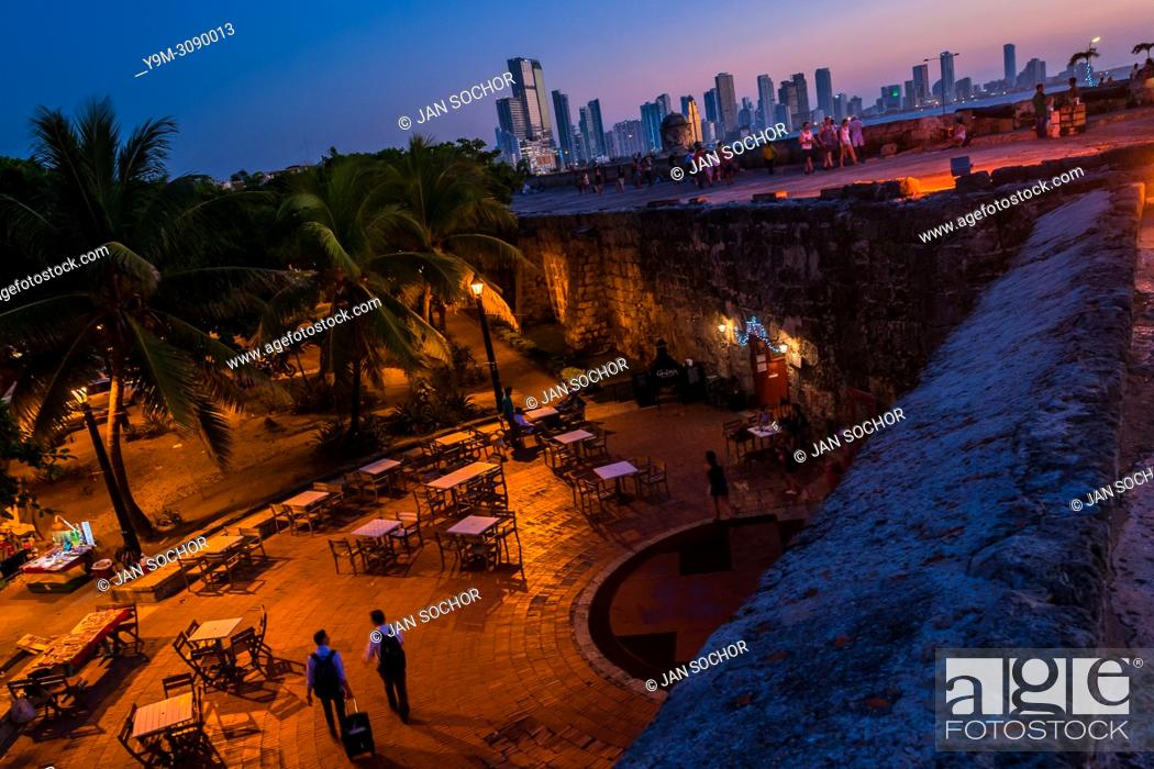 Stock Photo: Tourists walk on and along the stone walls, surrounding the colonial Walled City, at twilight in Cartagena, Colombia, 15 December 2017.