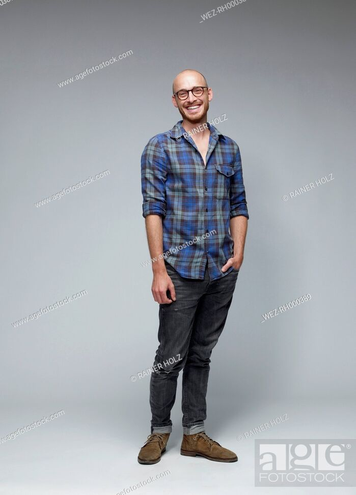 Stock Photo: Portrait of laughing man with hand in his pocket in front of grey background.