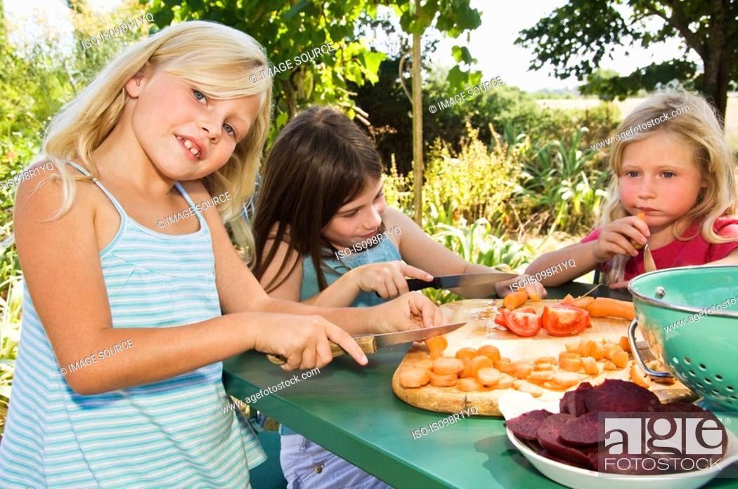 Stock Photo: Girls preparing vegetables.