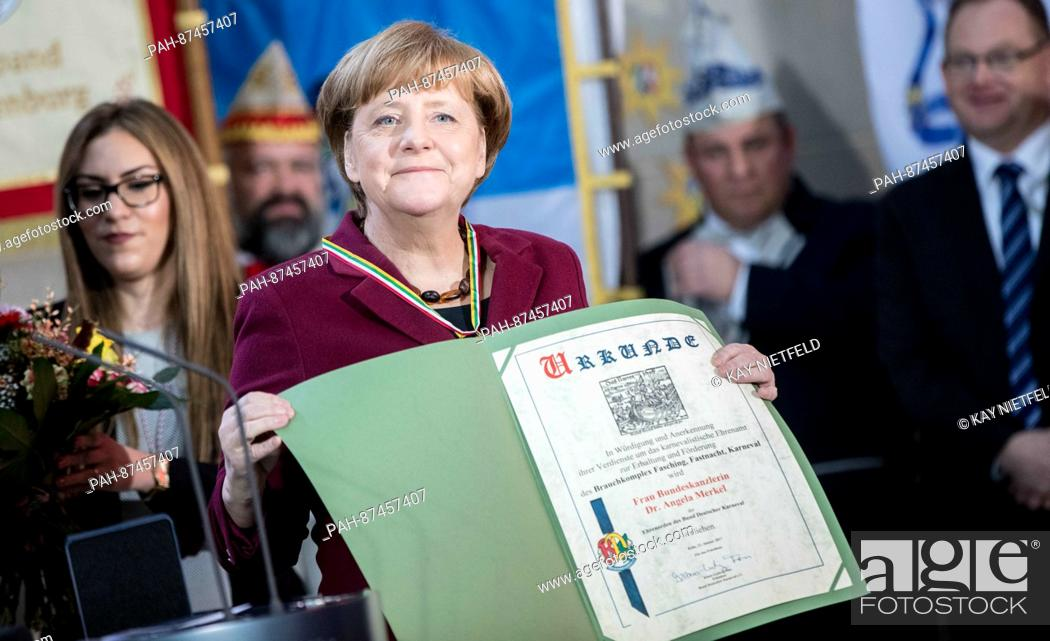 Stock Photo: German Chancellor Angela Merkel (CDU) welcomes the 'royal couples' from all states and holds up the certificate she received from the president of the German.