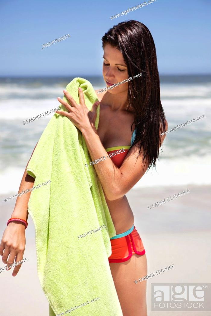 Stock Photo: Woman wiping her body with towel on beach.