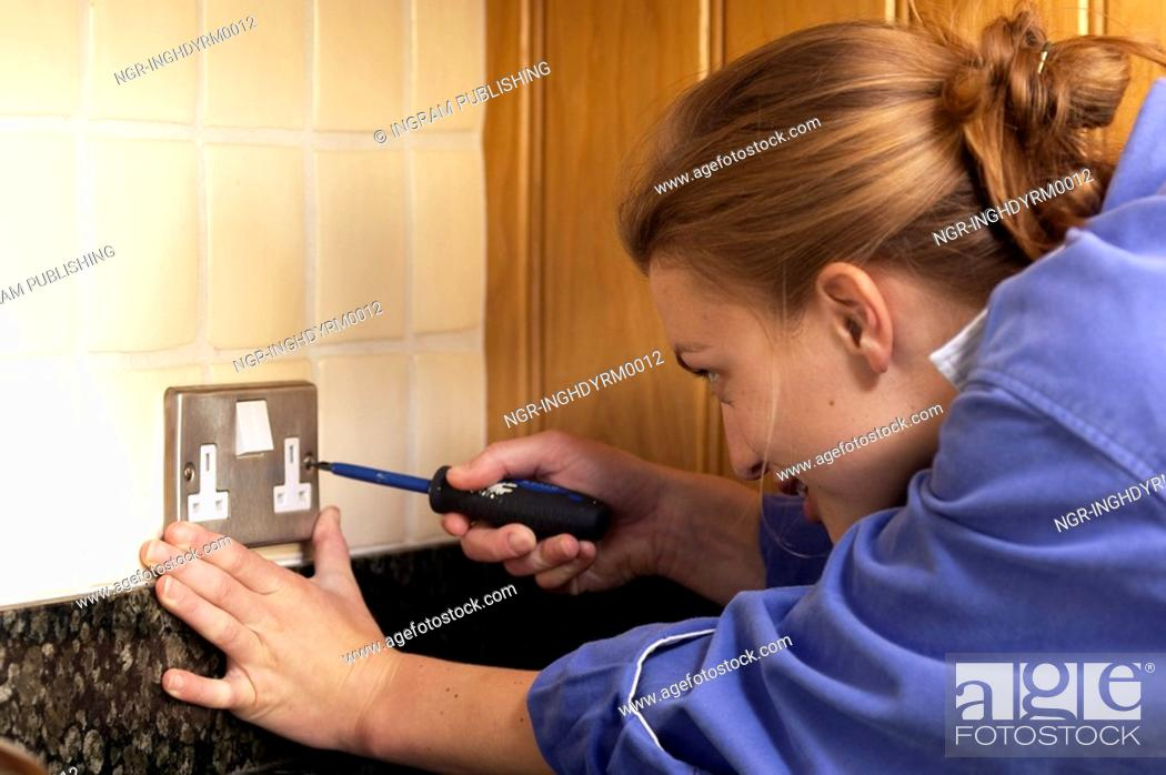 Stock Photo: Close-up of a young woman opening an electric switch with a screwdriver.