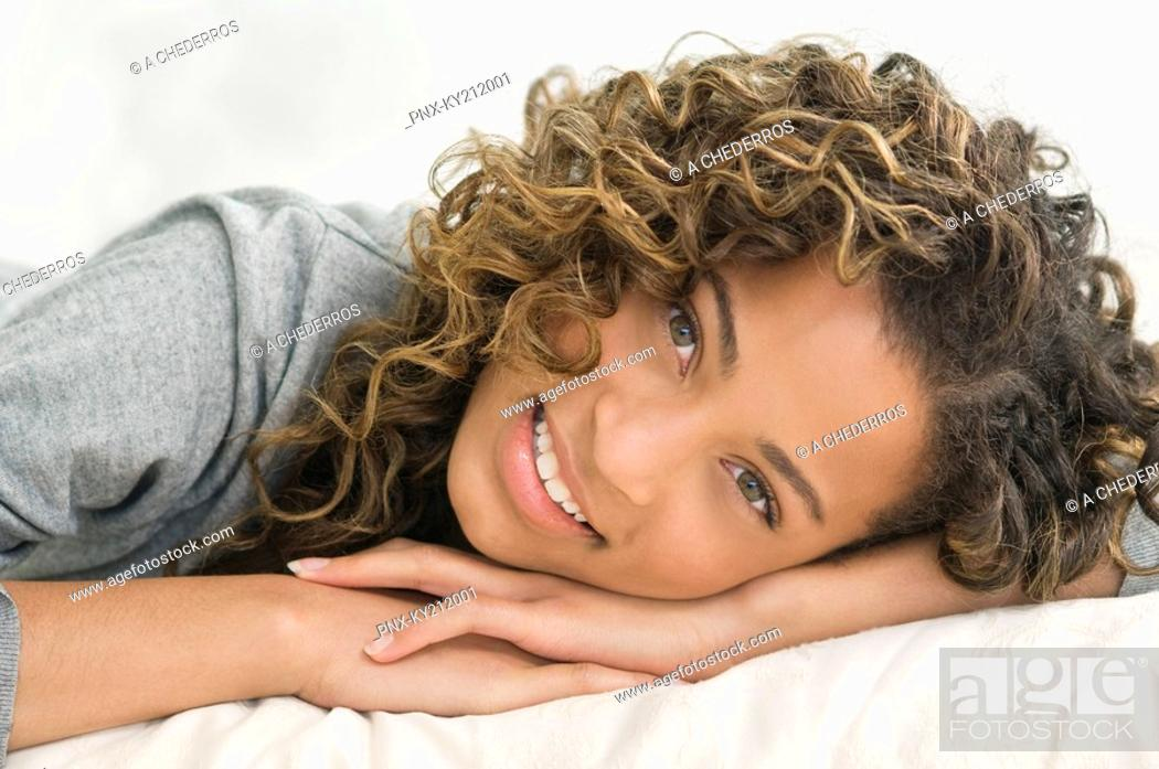 Stock Photo: Girl lying on the bed and smiling.
