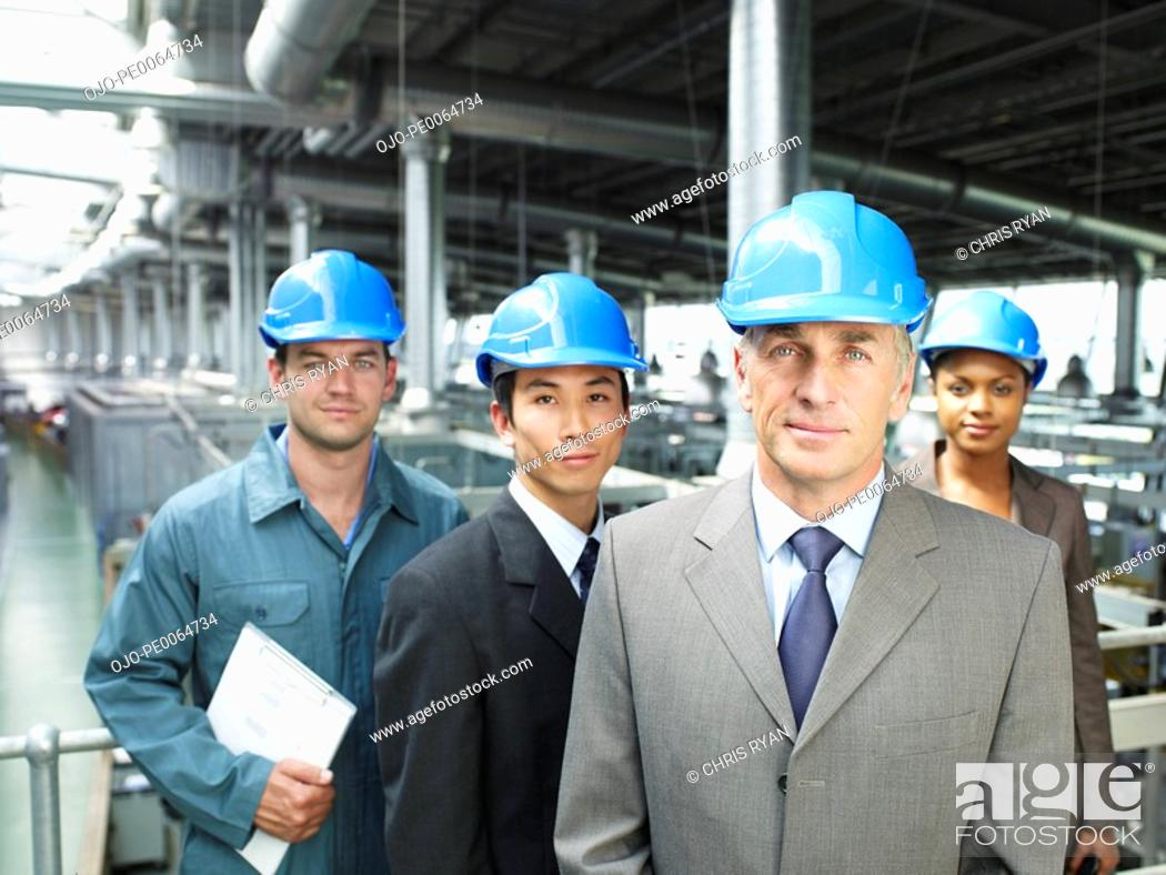 Stock Photo: Businesspeople wearing hard-hats in warehouse.