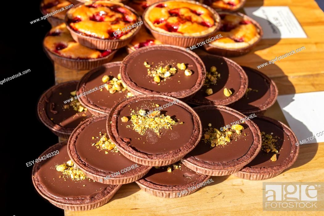 Stock Photo: Chocolate and pistachio tarts on display on a market stall in the UK.