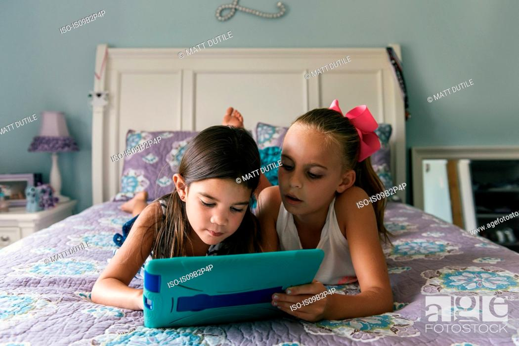 Imagen: Girls lying on bed using digital tablet.