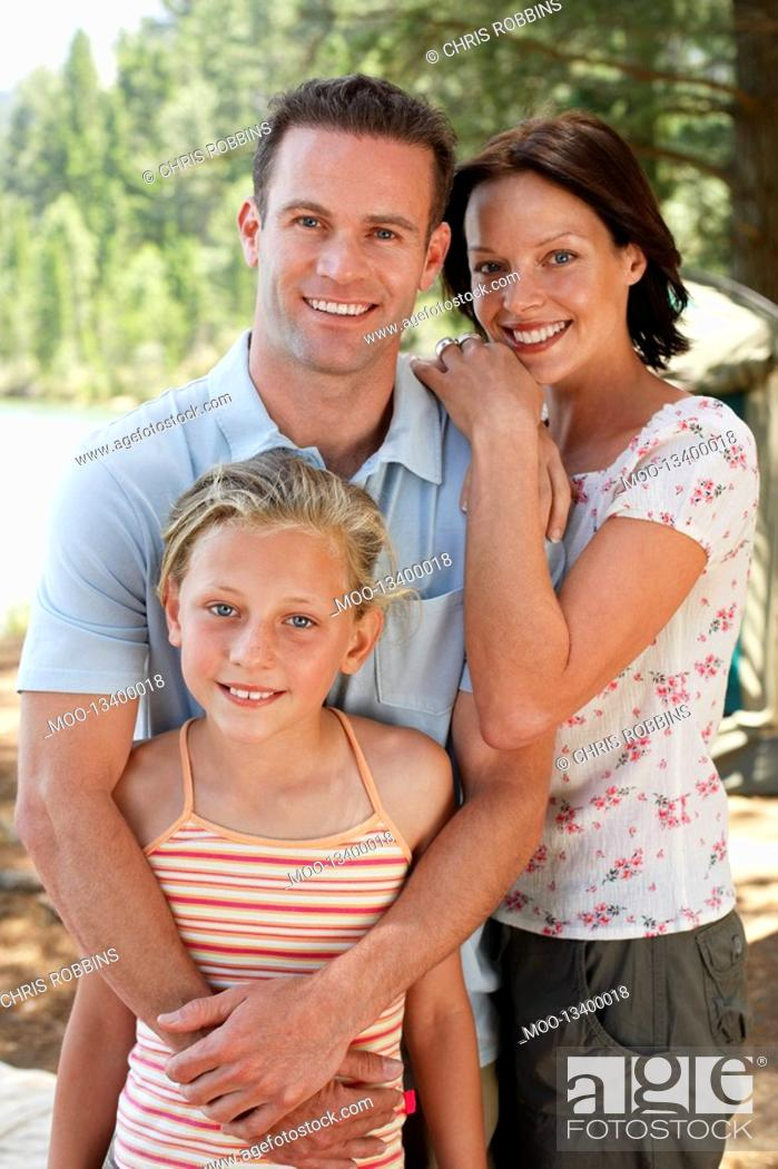 Stock Photo: Girl 7-9 standing outdoors with mother and father.