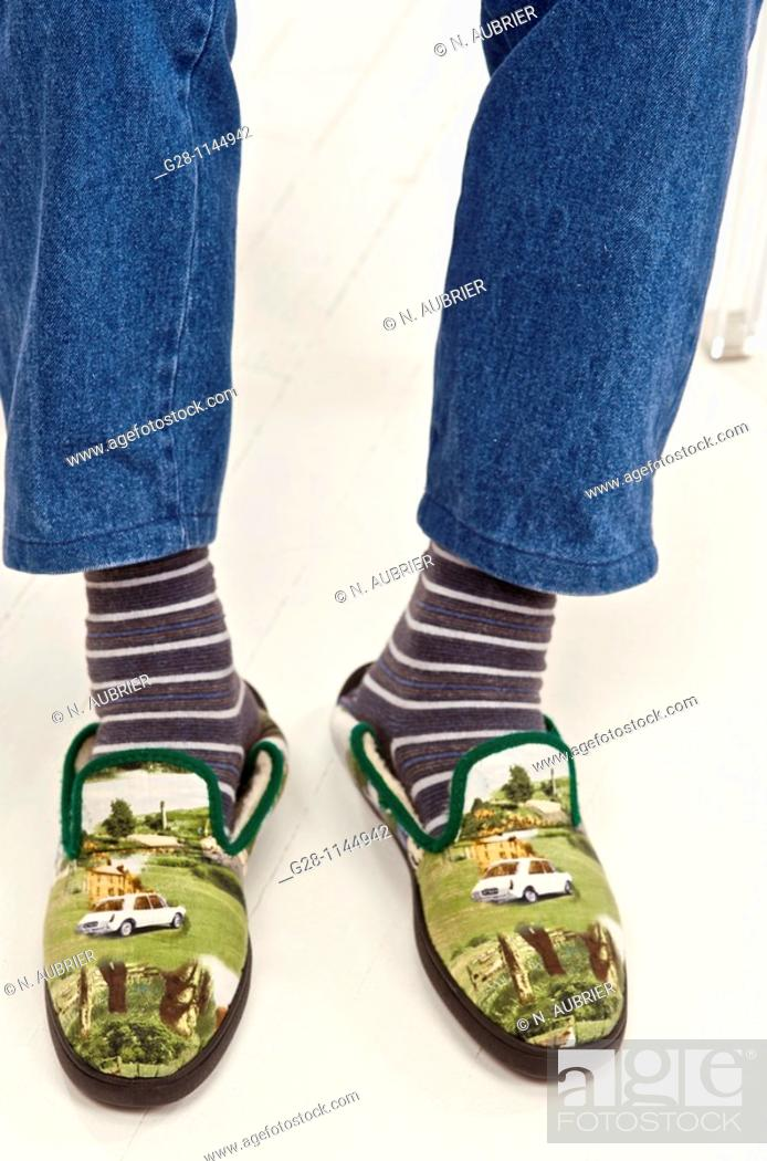 Stock Photo: Two feet in striped socks and funny comfortable slippers retirement and comfort concept.
