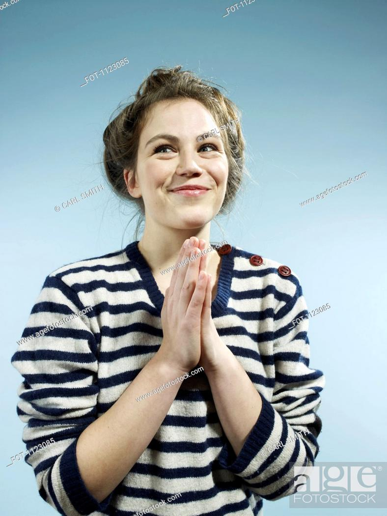 Stock Photo: A young woman with her hands together with a look of excited hope.