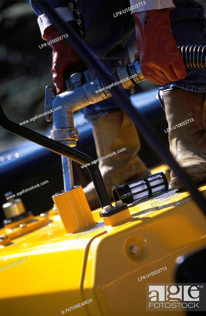 Stock Photo: Plant hire opertor filling petrol tank.