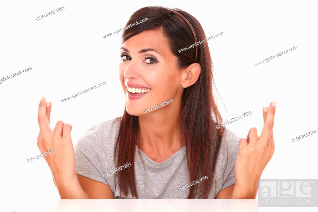 Imagen: Headshot portrait of attractive lady crossing her fingers while smiling and looking at camera on isolated studio.