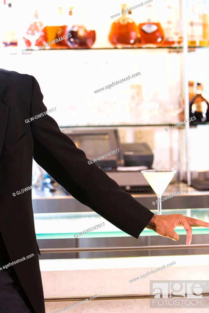 Stock Photo: Mid section view of a businessman standing at a bar counter.