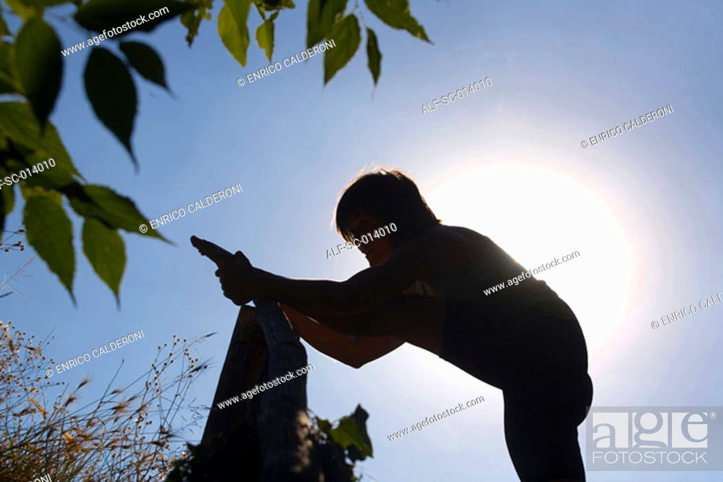 Stock Photo: Young woman silhouetted against sun.