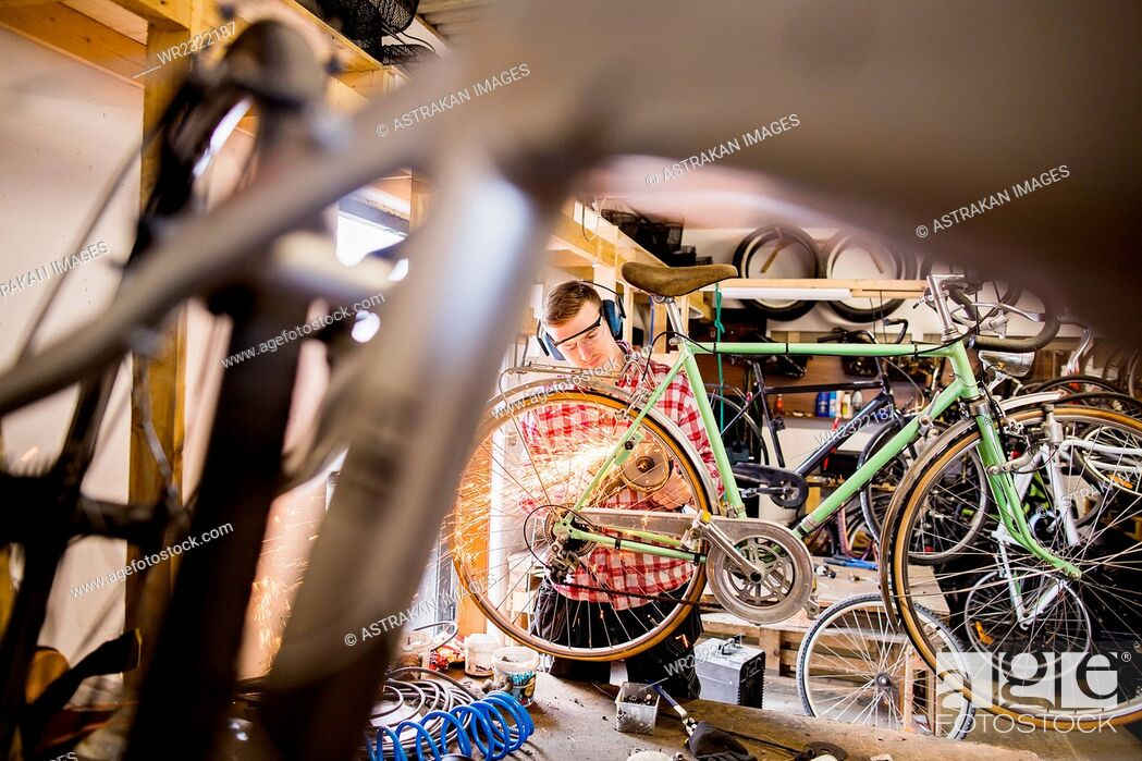 Stock Photo: Repairman using welding torch on bicycle in workshop.