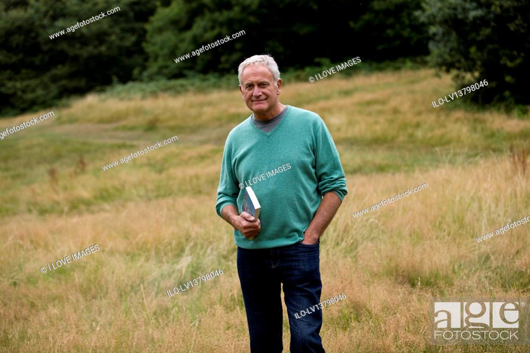 Stock Photo: A senior man standing in a field, holding a book.