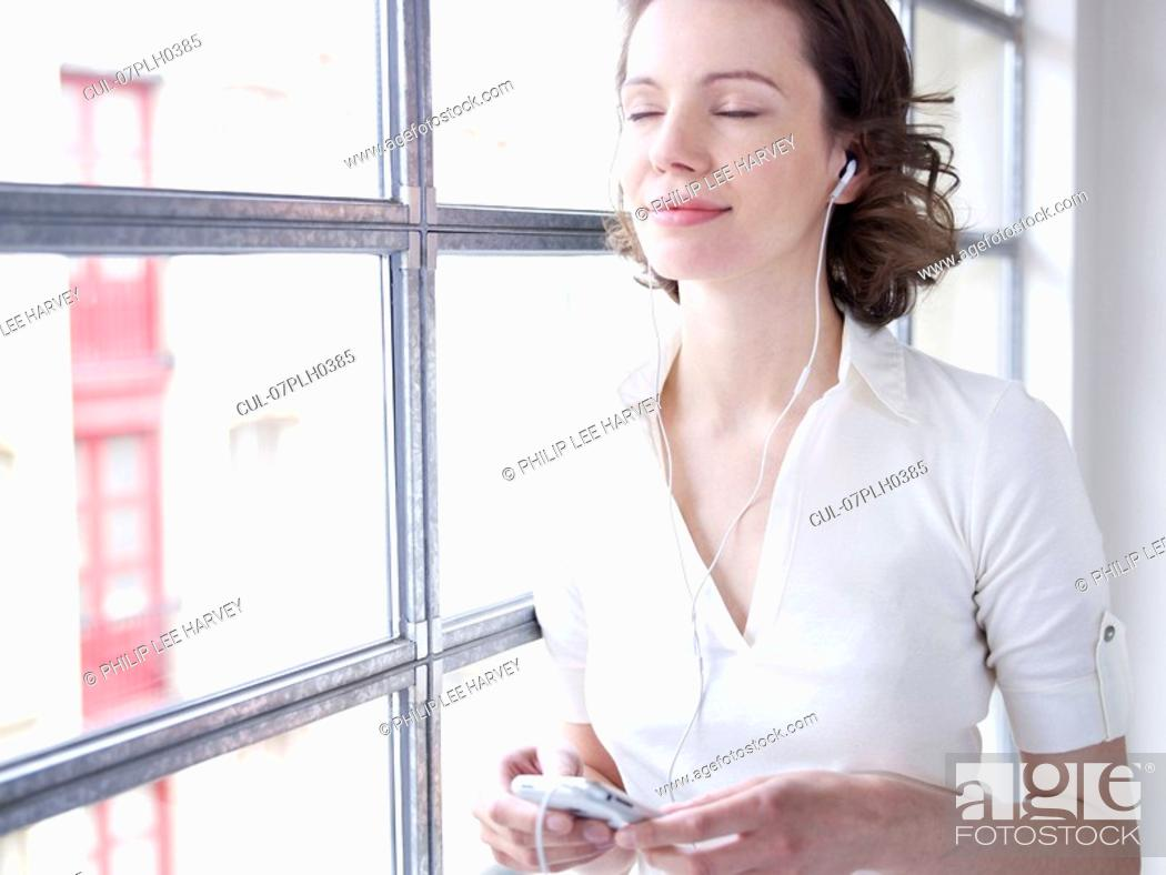 Stock Photo: Woman at window, listening to music.