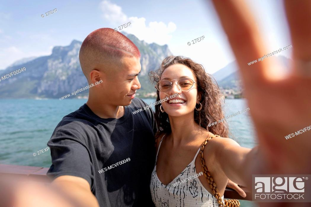 Stock Photo: Young couple taking selfie in front of Lake Como, Lecco, Italy.