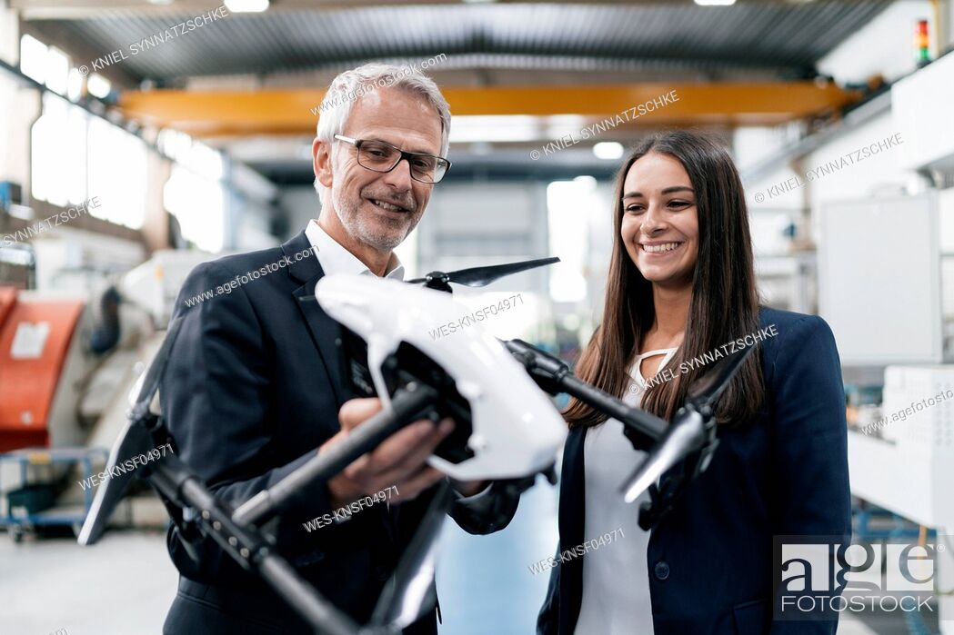 Stock Photo: Businessman an woman in high tech enterprise, discussing production of drones.
