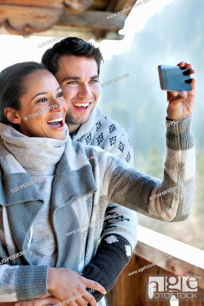 Stock Photo: Smiling couple taking self-portrait with camera phone on cabin porch.