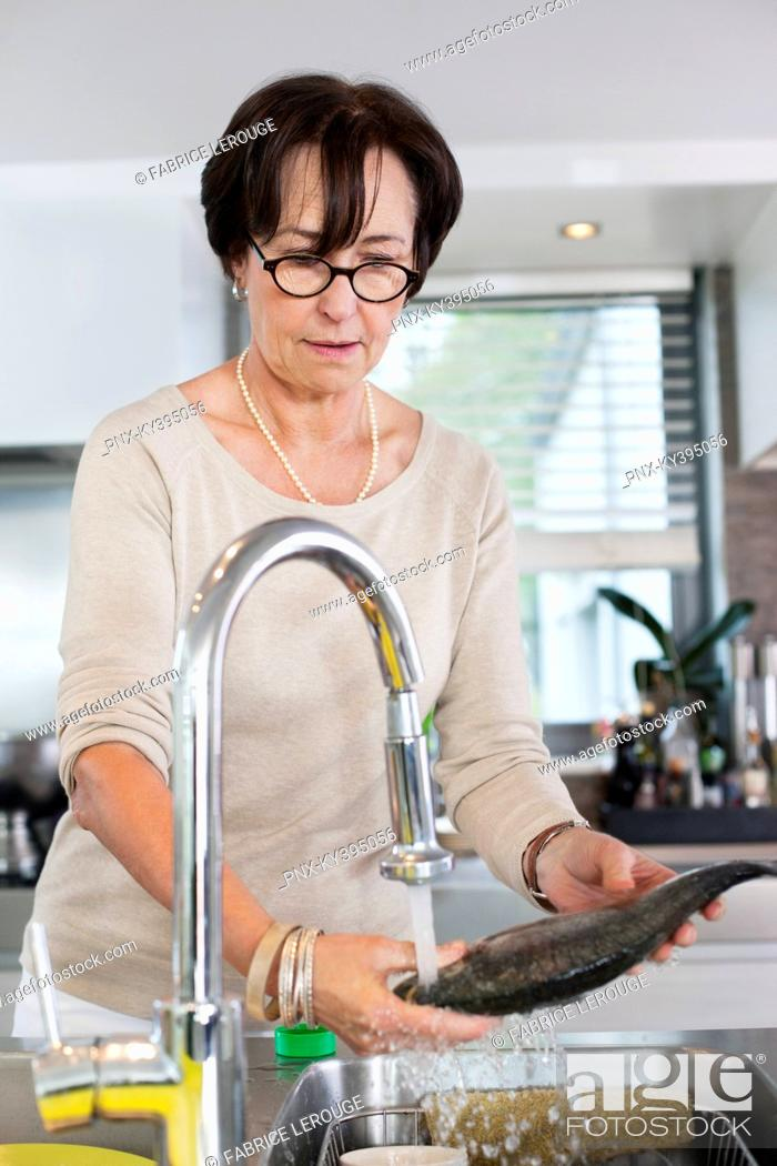 Stock Photo: Elderly woman washing a fish in a kitchen sink.