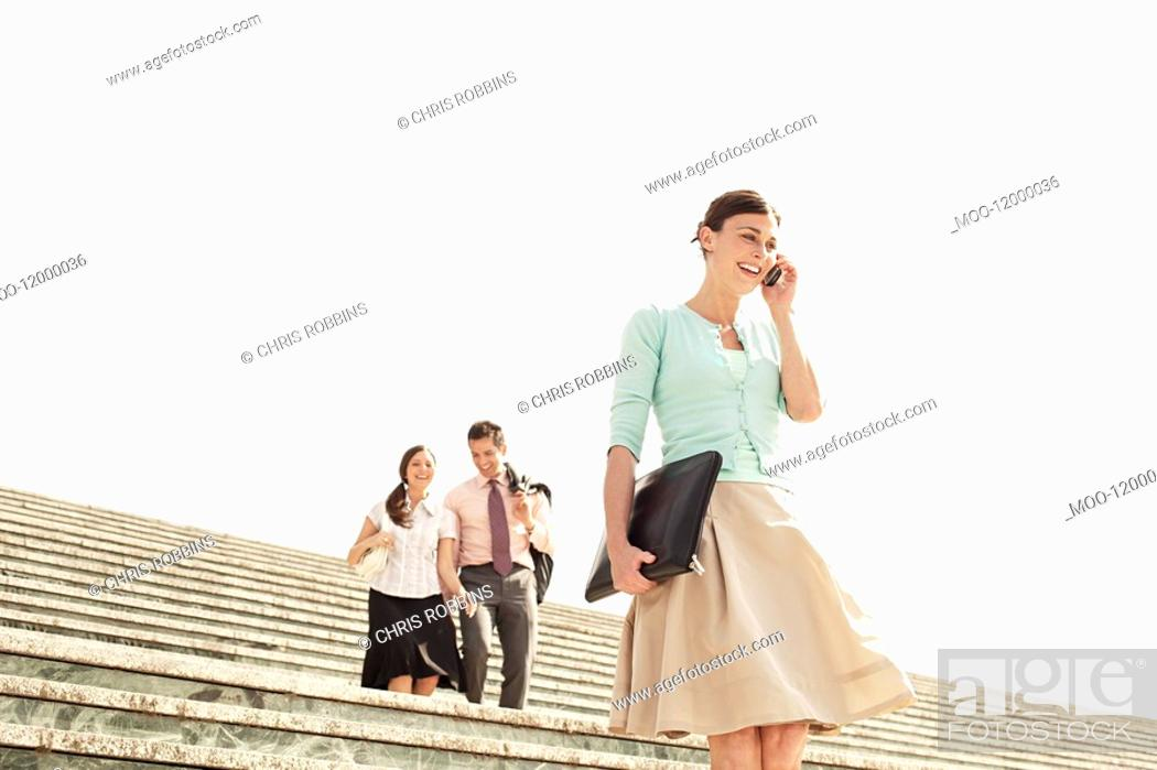 Stock Photo: Three office workers walking down steps woman in foreground using mobile phone low angle view.