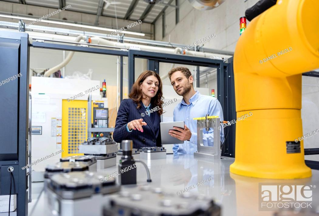 Stock Photo: Colleagues in high tech company controlling industrial robots, using digital tablet.