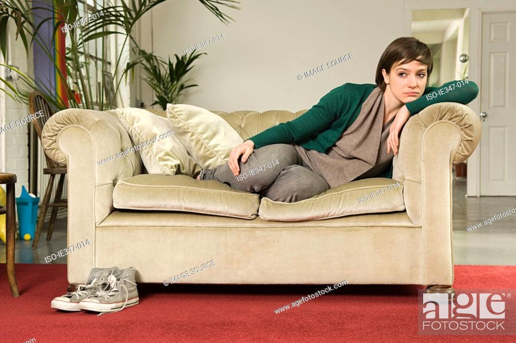 Stock Photo: Sullen young woman on sofa.