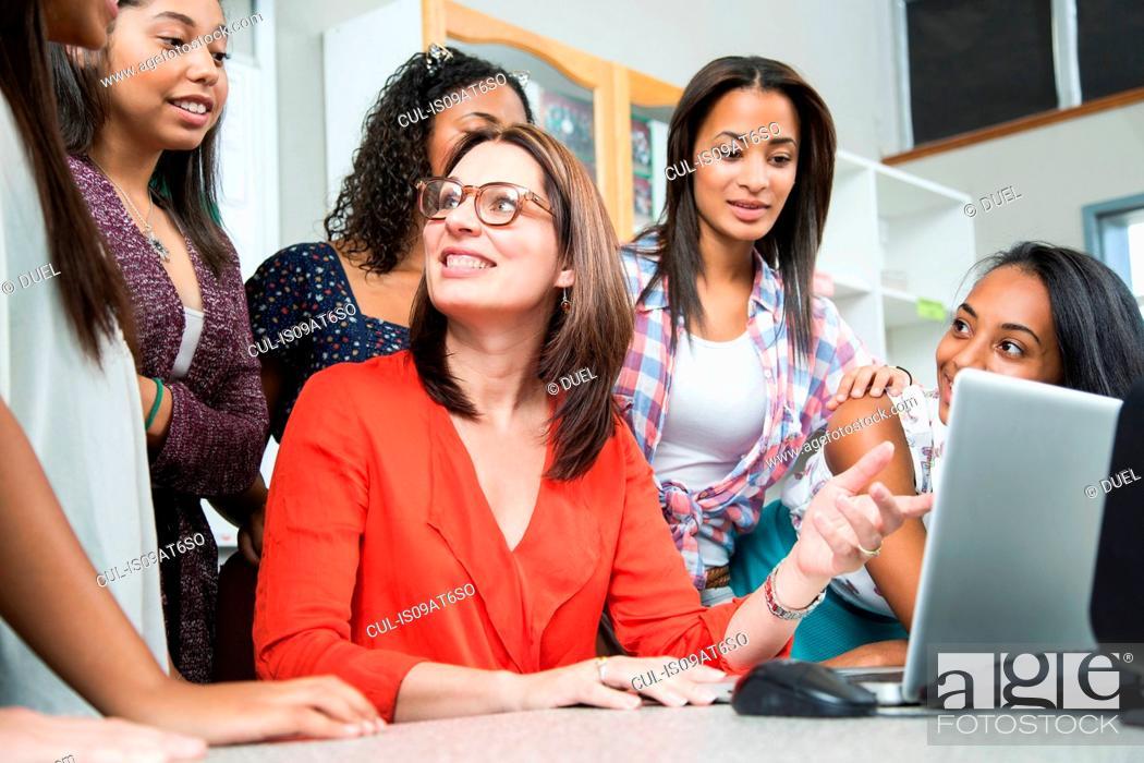 Stock Photo: Female teacher explaining on laptop to high school students.