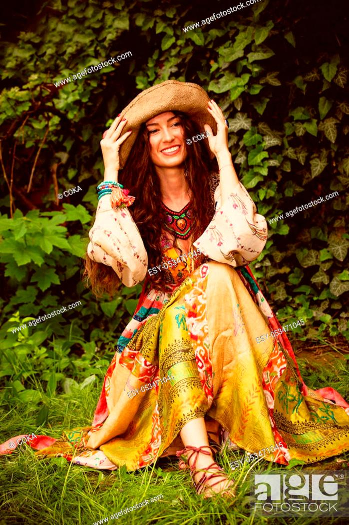 Stock Photo: young smiling woman in romantic summer dress and hat sit on grass in garden.
