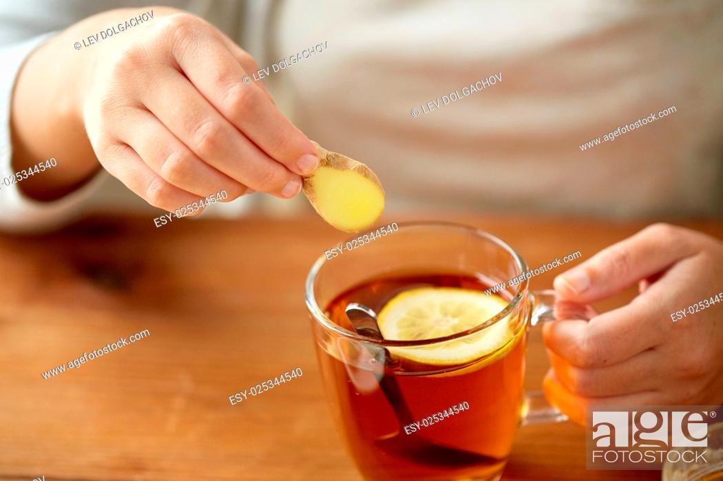 Stock Photo: health, traditional medicine and ethnoscience concept - close up of woman adding ginger to tea cup with lemon.
