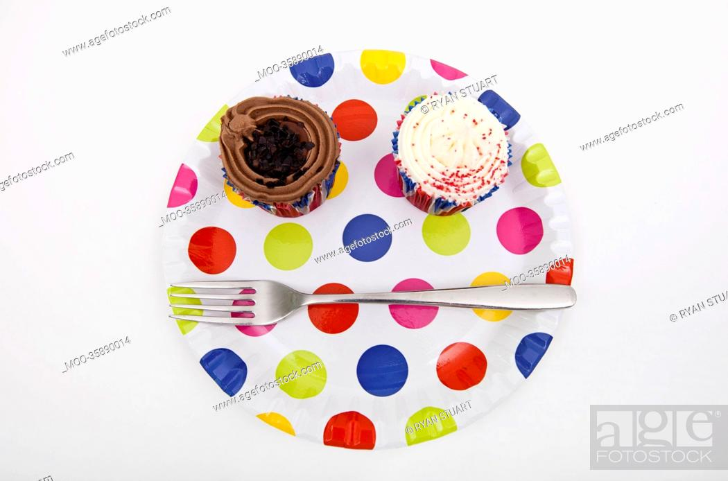 Stock Photo: Top view of cupcakes in multicolored plate over white background.
