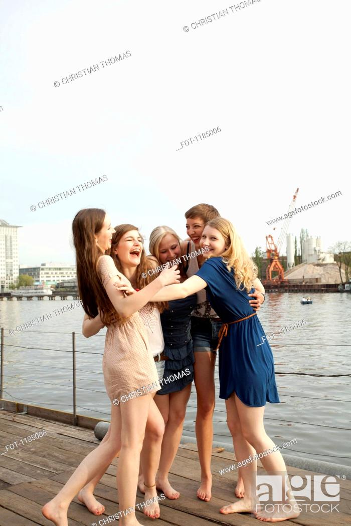 Stock Photo: Five female friends embracing and laughing, Spree Rive, Berlin, Germany.
