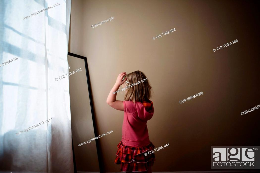 Young girl adjusting hairband in bedroom mirror, Stock Photo ...