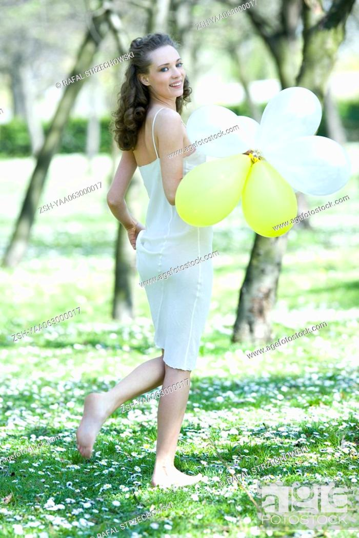 Stock Photo: Young woman walking barefoot in meadow, holding balloons, smiling over shoulder at camera.