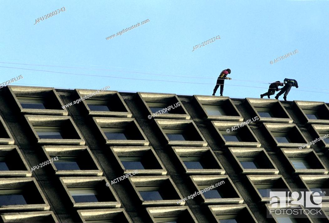 Stock Photo: Three men abseiling a building.