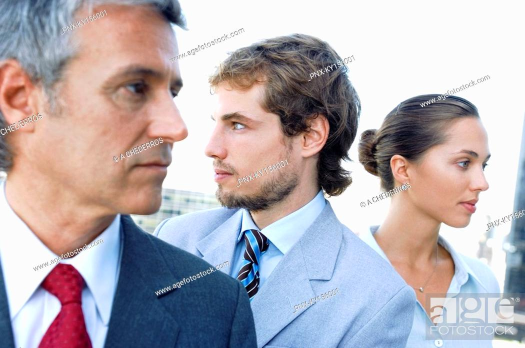 Stock Photo: Business people in row, looking away, close-up.