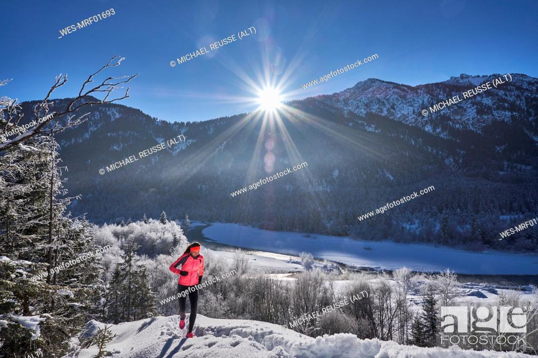 Stock Photo: Germany, Bavaria, Isar valley, Vorderriss, woman jogging in winter.