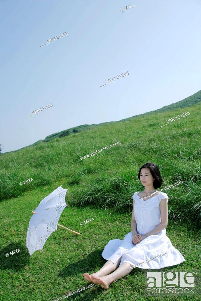 Stock Photo: A young woman sitting on grass field.