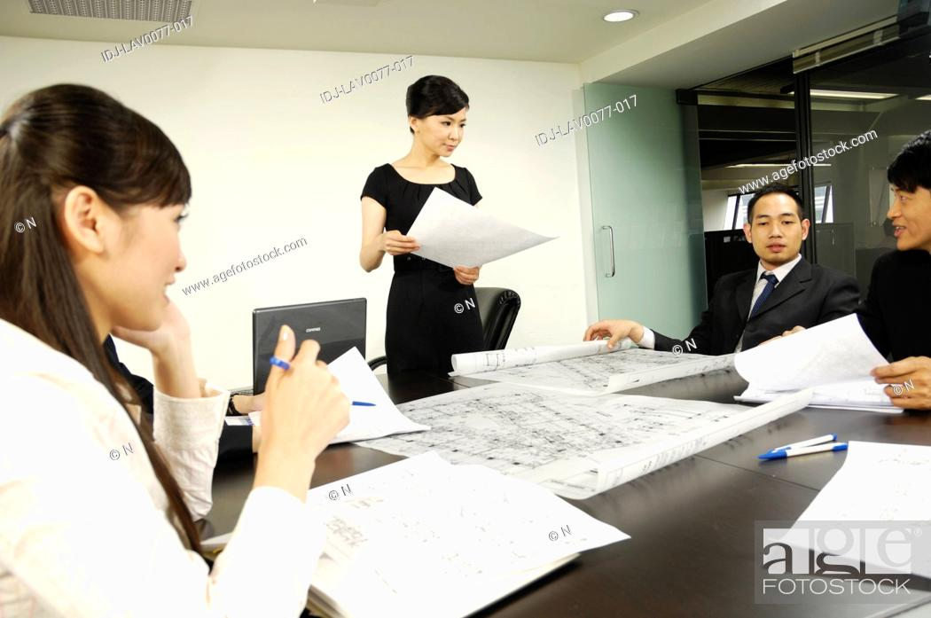 Stock Photo: Architects discussing blueprints in a conference room.